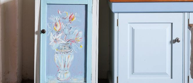 flower Cupboard painted by Caroline Ede in the kitchen at Rough Acre